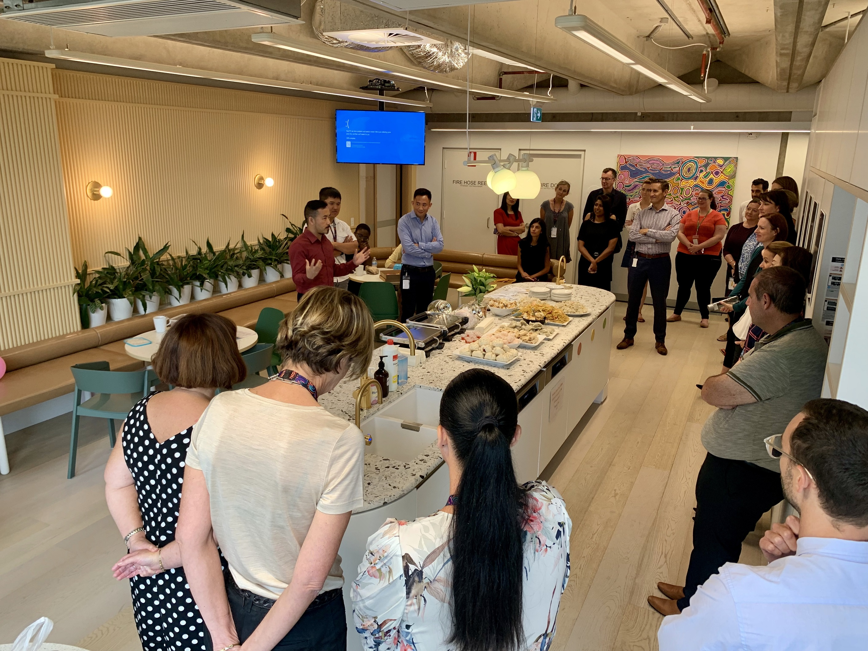 employees standing in the kitchen for a culture presentation